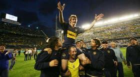 Ricardo Noir, de 21 años, en andas de Cacho Laudonio, el utilero de Boca, y rodeado de muchos jugadores de las inferiores