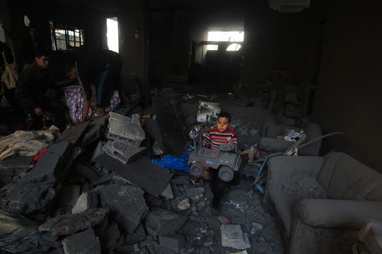Una familia palestina trata de recuperar de los escombros algunas de sus pertenencias luego de un ataque israelí. Foto: AFP