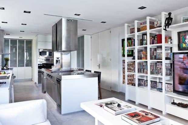 """""""Frente a tanta tecnología en la cocina, el living debía equilibrar con calidez; por eso elegimos hacer una biblioteca que reuniera libros, música, juegos y películas. La idea fue desestructurar la imagen minimalista y dar un clima de reunión y bienvenida"""", resume Yankelevich.  /Javier Picerno"""
