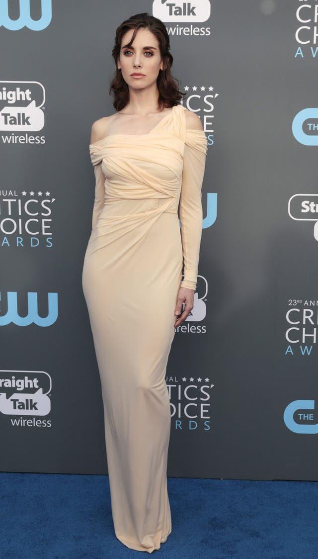 Alison Brie con un vestido en color crudo, y ajustado, el modelo es de Roberto Cavalli