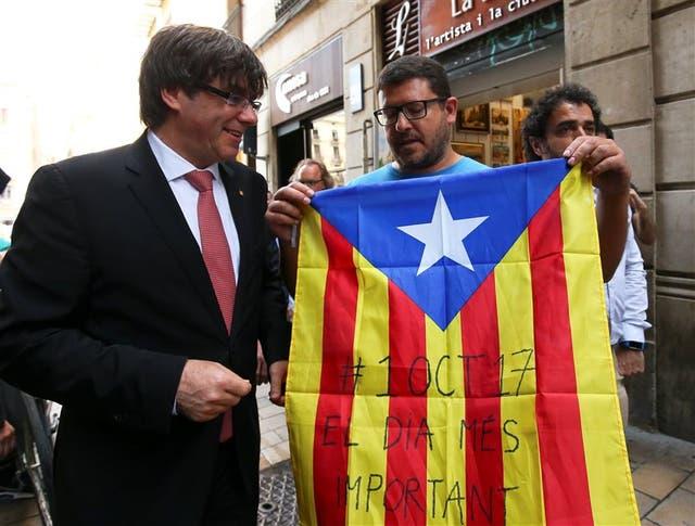 Puigdemont, junto a un catalán con la bandera regional y la fecha del referéndum