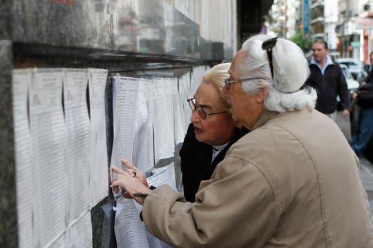 Dos mujeres busca su nombre en los padrones. Foto: AP