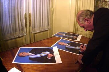 De la Rúa firma fotografías en diciembre de 2001, justo antes de su salida anticipada del Gobierno