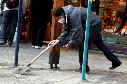 Un hombre remueve las cenizas hacia la calle para que luego pueda ser recogida por las máquinas de limpieza de la ciudad. Foto: Reuters