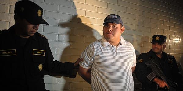Dos agentes de policía custodian a Elkin Vargas, uno de los presuntos implicados en el asesinato del cantante y compositor argentino Facundo Cabral