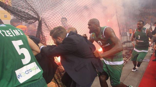 Los jugadores de Panathinaikos se escapan en medio de la agresión de los hinchas de Olympiacos