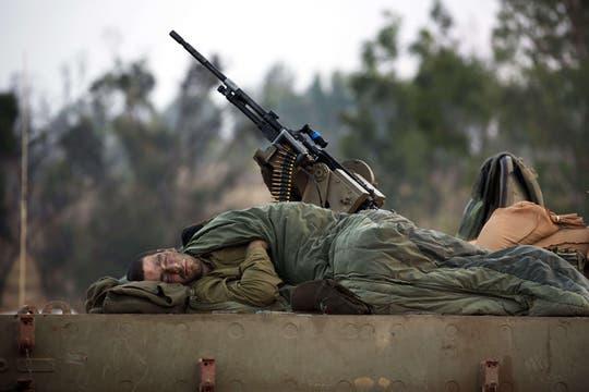 Un soldado israelí duerme en la parte superior de un tanque en una zona de despliegue del ejército israelí cerca de la frontera entre Israel y la Franja de Gaza. Foto: AFP