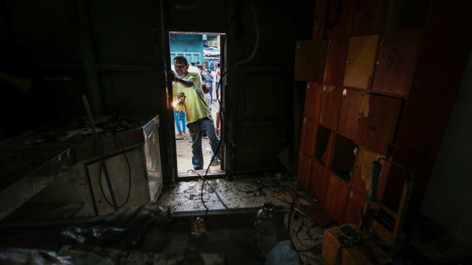 Un empleado arregla la puerta de un local. Foto: Reuters / Fernando Llano