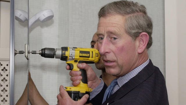 Posa con un taladro en la mano durante una visita a un jóven ganador del Prince's Trust Grant, que ayudaba a los jóvenes iniciar negocios, junio de 2002