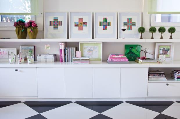 Un largo mueble aloja libros de arte, de cocina, cuentos infantiles y cuatro acrílicos de Javier Casals de la serie Cruces..