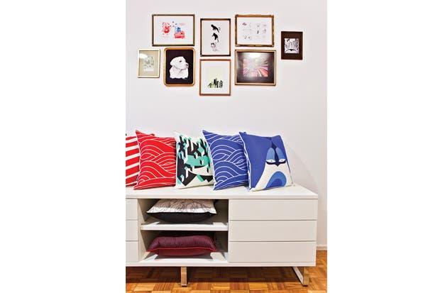 el mueble bajo 'Greta' con cajones en laca poliuretánica semimate (Neoda) exhibe varios modelos de almohadones (Abunda)..