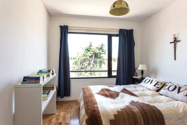 """""""Al dormitorio no quisimos llenarlo demasiado"""". Por eso, apenas se colocó allí una mesa práctica y multiuso (que eventualmente puede servir para apoyar una pantalla), mesas de luz y por supuesto la cama, vestida con una manta de llama.  /Daniel Karp"""