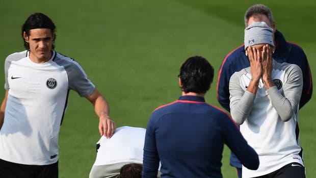 Cavani y Neymar escuchan a Emery, durante el entrenamiento de este martes