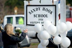 Una mujer llora en la puerta del colegio Sandy Hook, lugar de la masacre de ayer