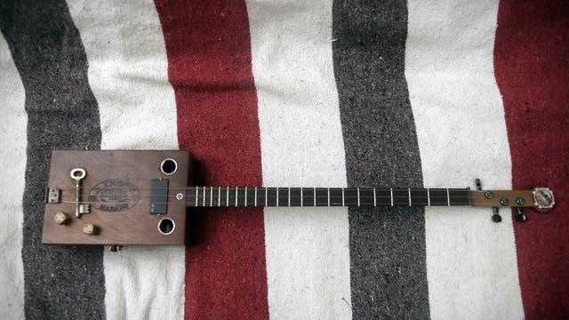 Detalle de la guitarra de tres cuerdas hecha a partir de una caja de cigarros