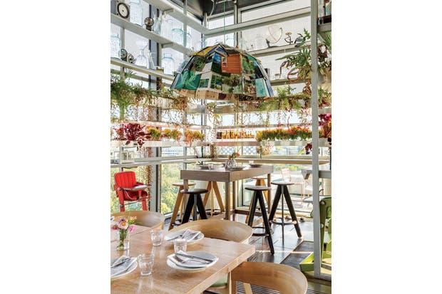 En el restaurante Neni, un rincón verde con espíritu de laboratorio: cultivo y elaboración de los alimentos en el mismo espacio. La gran pantalla hecha de libros pertenece a una edición limitada de Aisslinger, que en esta ocasión la armó, lógicamente, sólo con libros de jardinería.  Foto:Living /Daniel Karp