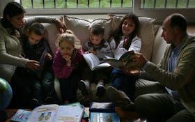 Silvina Kerr y su marido les enseñan a sus hijos en el living familiar