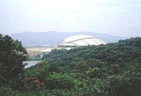 Vista de la blanca porción de la esfera de El Gran Ojo, que emerge de entre las verdes colinas del Parque Deportivo