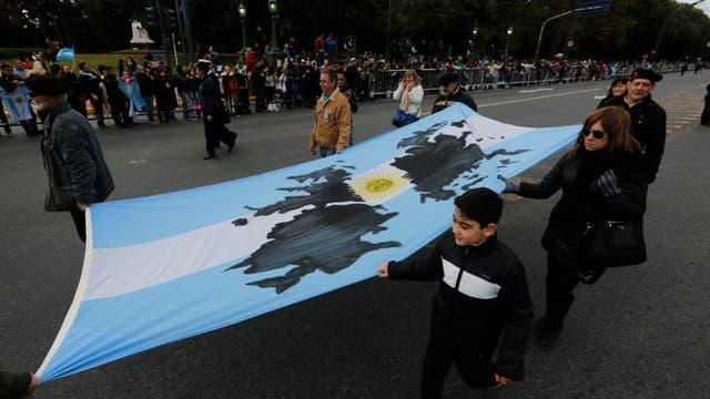 Algunos de traje, otros con uniformes de combate, algunos de la mano con sus hijos y nietos, todos los ex combatientes recibieron orgullosos el aliento de los que esperaban con banderas y cámaras de fotos para verlos pasar