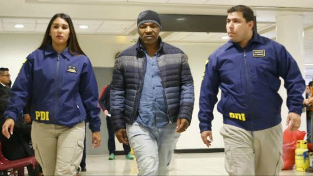Mike Tyson. escoltado por dos oficiales de policía en el aeropuerto de Santiago, Chile. El ex campeón de los pesados tampoco pudo entrar en nuestro país