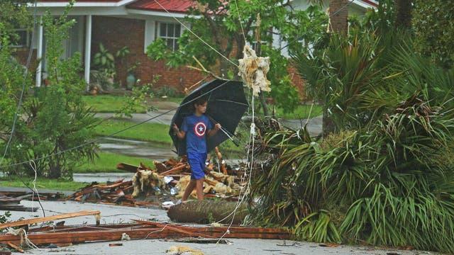 Aden Alcroix-Camper, de 11 a?os, camina a través de los escombros de un tejado en en Palm Bay, Florida