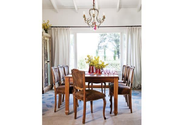 Alrededor de la mesa de comedor heredada, juego de sillas retapizadas (La Tiendita). Roperito antiguo decapado (El Galpón). Las cortinas de algodón (La Tiendita) aplacan algo la luz del día..
