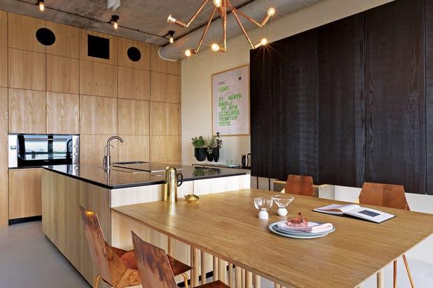 En el lateral, modular 'Natural Skin' con frente de madera termotratada, que aloja con elegante sutileza cajoneras, estantes, cestos y electrodomésticos, ubicados de manera funcional.  /Gentileza Minacciolo