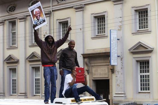 Tres hombres esperan sobre el techo de un colectivo el paso del coche fúnebre que traslada a Mandela. Foto: EFE