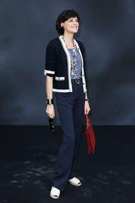 Inés de la Fressange, siempre impecable, con un cardigan tejido color azul marino y larguísimos collares de perlas. Foto: Chanel Latin America