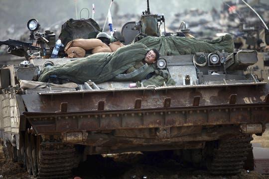 Soldados israelíes duermen sobre tanques Merkava  en una zona del sur de Israel, situada a lo largo de la frontera con la Franja de Gaza. Foto: EFE