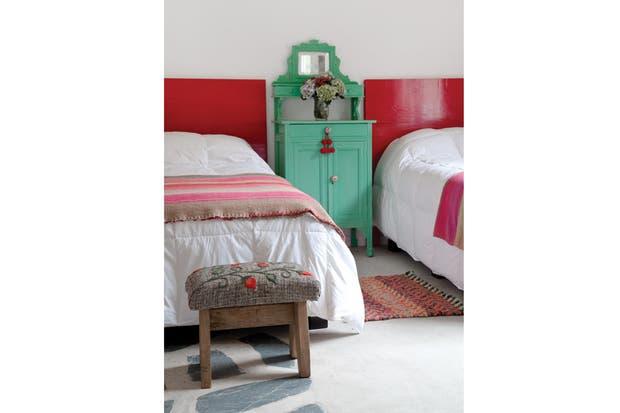 Camas con espaldares rojos de madera laqueada; al pie, mantas de Tilcara. La mesa de luz contrastante -de herencia familiar- y los banquitos (Carolina Hardoy)..