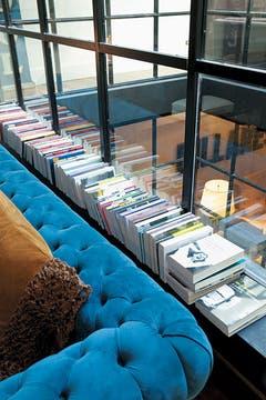 Junto a las ventanas, bordeando los sofás del gran living, cientos de libros, una manera de poner el placer de la lectura al alcance de la mano y con luz natural. Foto: Adela Aldama
