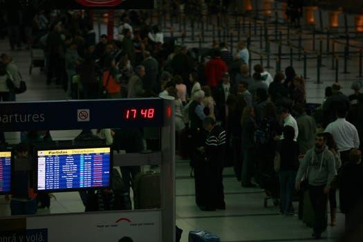 Varias personas hacen cola en el aeropuerto de Ezeiza para realizar el check-in de su vuelo que fue reprogramado tras haberse reanudado momentáneamente los vuelos el lunes 13 de junio. Foto: LA NACION / Graciela Calabrese