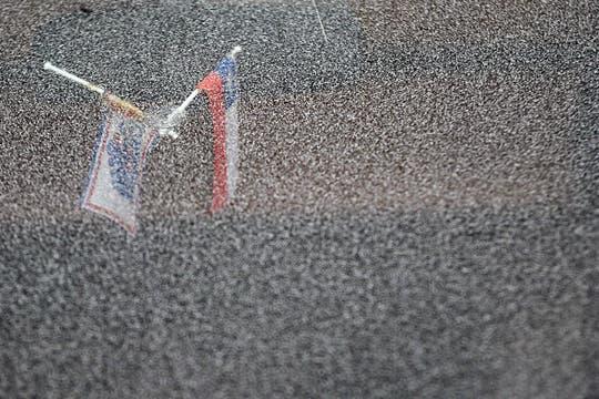 Vista de unas banderas durante una lluvia de cenizas, en la localidad de Lago Ranco, Chile. Foto: EFE