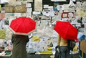 Bajo la lluvia, dos mujeres leen los mensajes que cientos de fanáticos le dejaron a Maradona