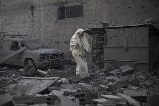 Una mujer palestina habla por teléfono móvil entre los escombros tras un bombardeo israelí que destruyó la vivienda de sus vecinos. Foto: EFE
