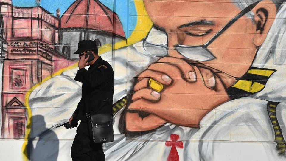 Un miembro de la seguridad habla por teléfono junto a un mural en Ecatepec. Foto: AFP