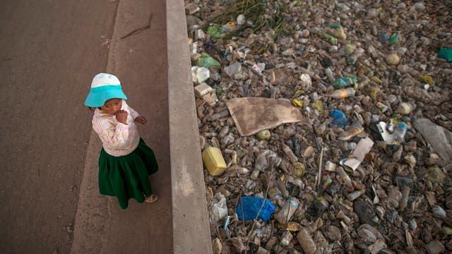 María José Campos Inquilla de pie junto al río Torococha lleno de basura cerca de una planta de tratamiento de residuos municipales que se alimenta en el Lago Titicaca, en Juliaca, en la región de Puno, Perú