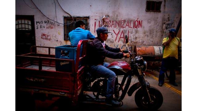 Una moto pasa adelante de un grafiti que dice