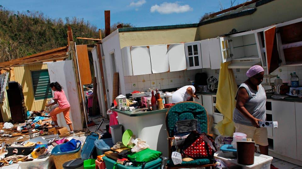 Una familia mira los restos de su casa. Foto: AFP / Ricardo Arduengo