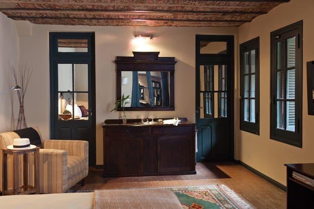 Aquí conviven muebles antiguos con artefactos modernos, como la lámpara de mesa y los veladores de pared que rodean la cama..