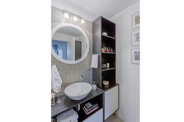 En sintonía con el vanitory de MDF existente, se hizo un mueble alto en el lateral, con estantes abiertos arriba y puerta debajo, para las toallas y artículos de tocador.  Foto:Living /Daniel Karp