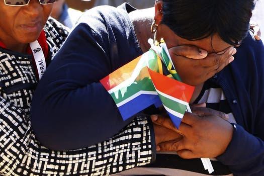 Una mujer, sin consuelo, llora tras el paso de la caravana. Foto: EFE
