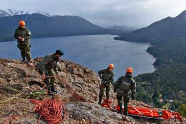 Cuatro gendarmes preparan las cuerdas y la camilla especial con la que descenderán, en forma vertical, por una pared de piedra.