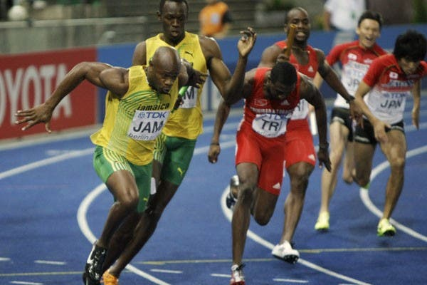 El cuarteto caribeño dominó la carrera; acá, Bolt le pasa el testimonio a Powell