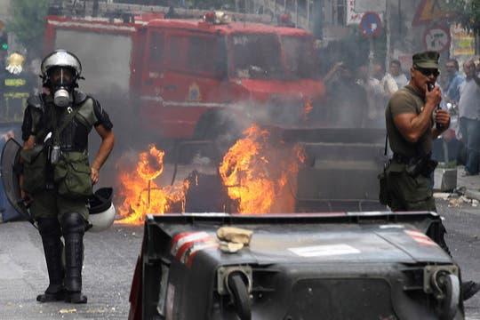 Policías antidisturbios permanecen junto a contenedores incendiados por manifestantes. Foto: EFE