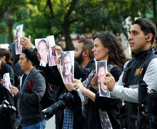 Peroidistas sostienen fotos de Valdez en una manifestación