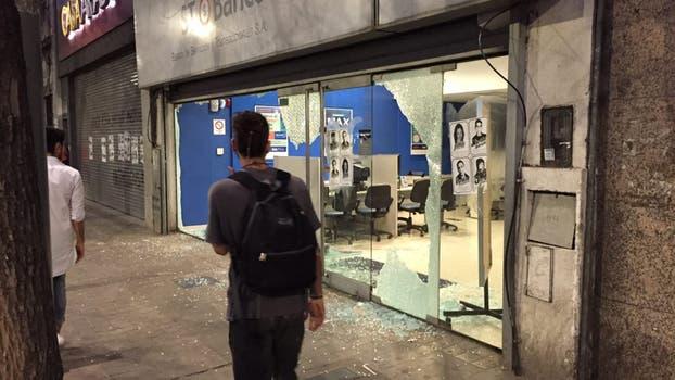 El episodio más violento fue cuando un grupo de encapuchados rompió las vidrieras de una financiera.