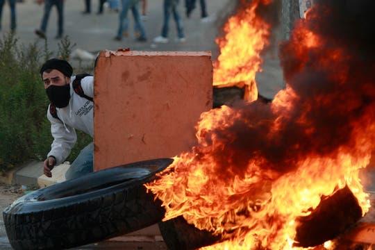 Un hombre se refugia durante los enfrentamientos. Foto: AP
