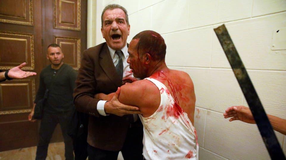 El legislador de la oposición Stefanelli sostiene a un partidario herido del gobierno luego de que él y un grupo de simpatizantes del gobierno irrumpieron en la Asamblea Nacional de Venezuela. Foto: Reuters / Carlos Garcia Rawlins